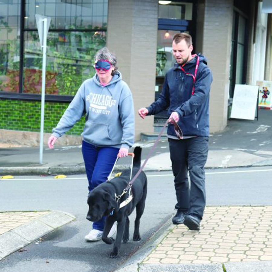 woman wearing a blindfold walking with a Guide Dog and man