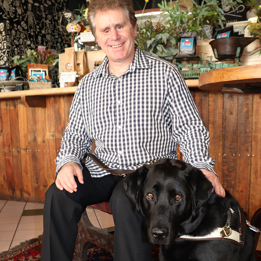 a smiling man and his Guide Dog
