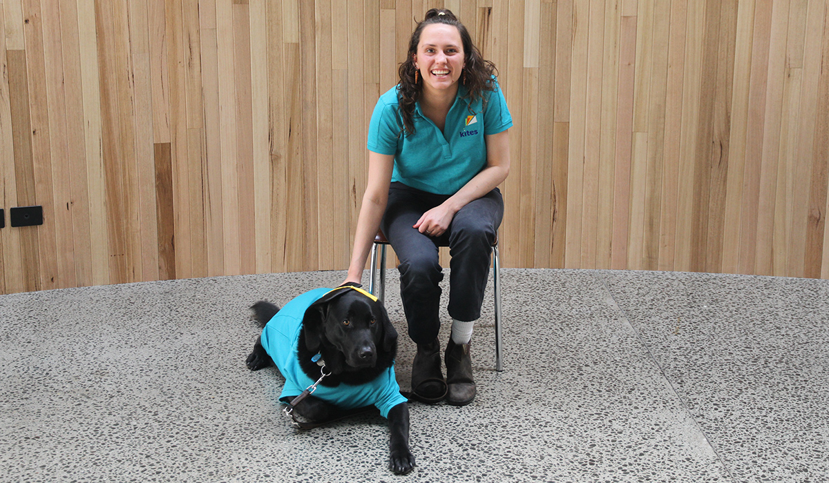 Smiling lady with a black dog wearing a motarboard