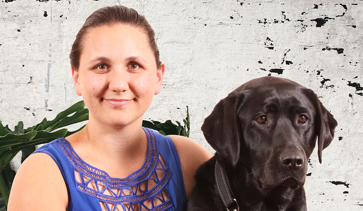 smiling woman with a guide dog