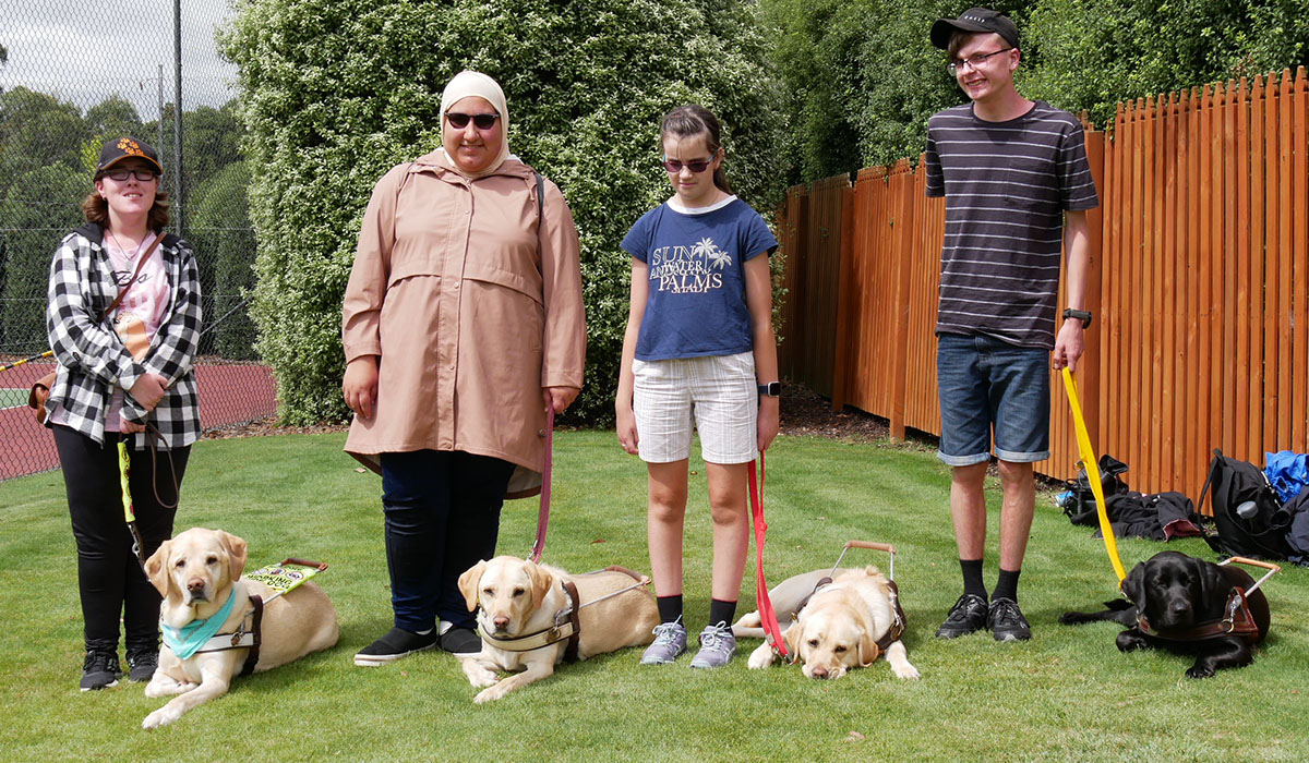four young people standing next to Guide Dogs