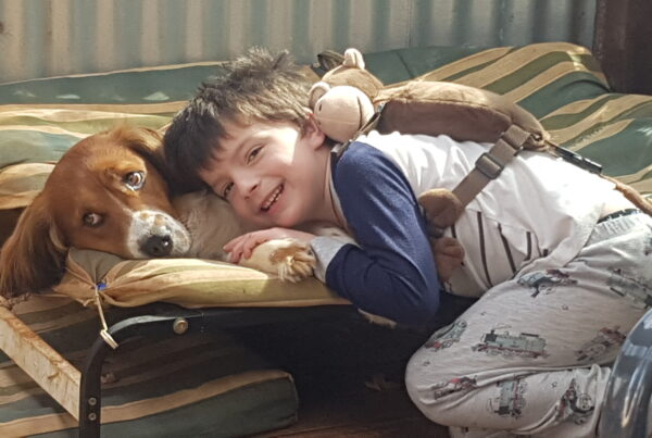 Little boy smiling, and laying next to a pet dog