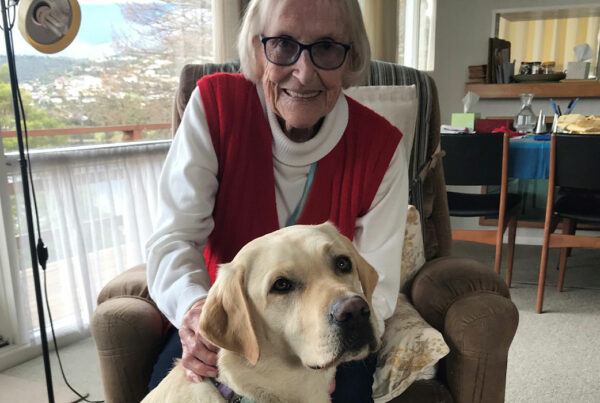 a smiling lady sitting behind a dog