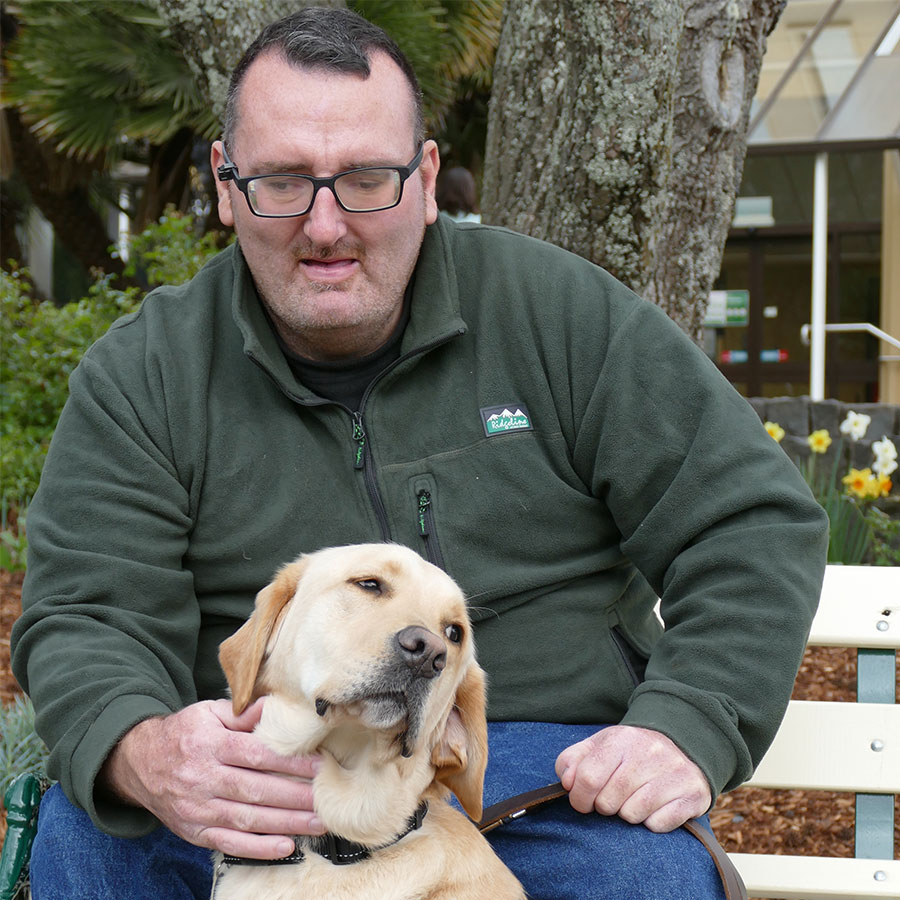 a man sitting behind his guide dog