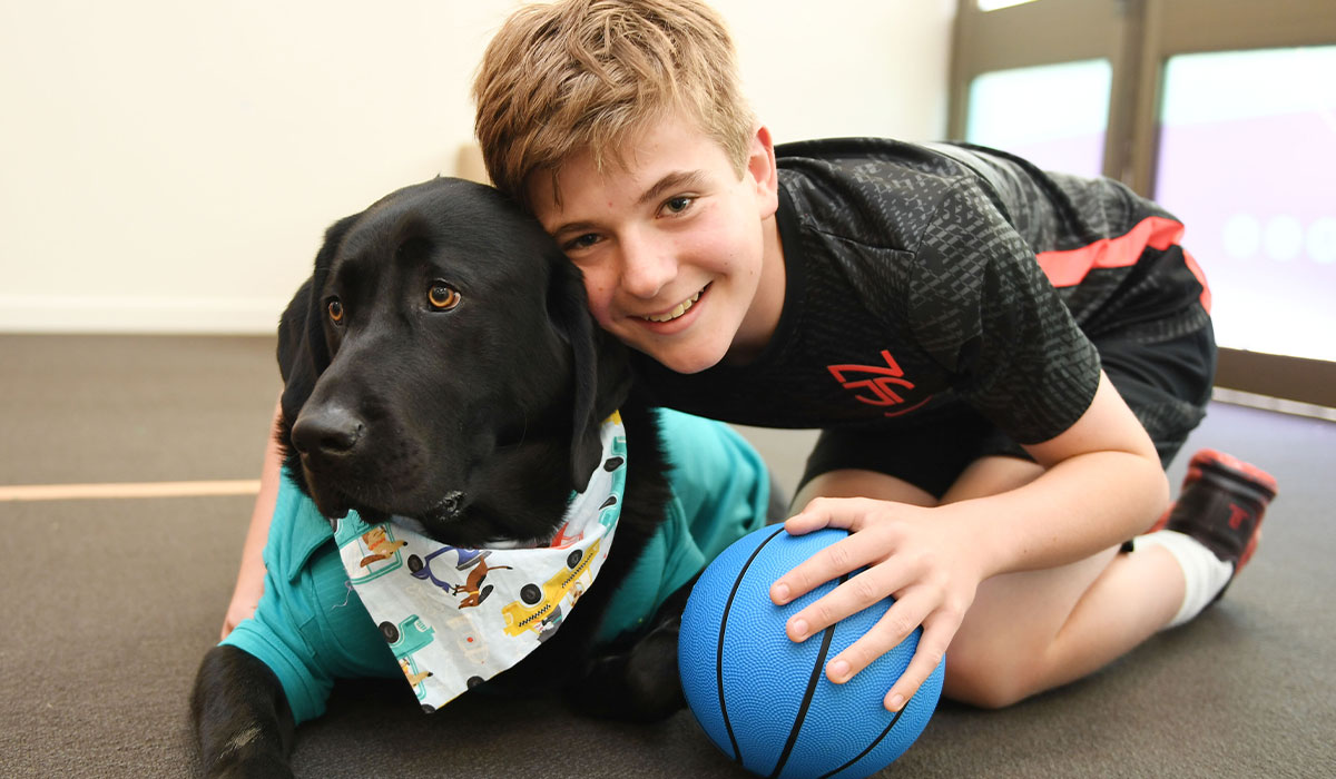 smiling young boy next to a dog in at shirt