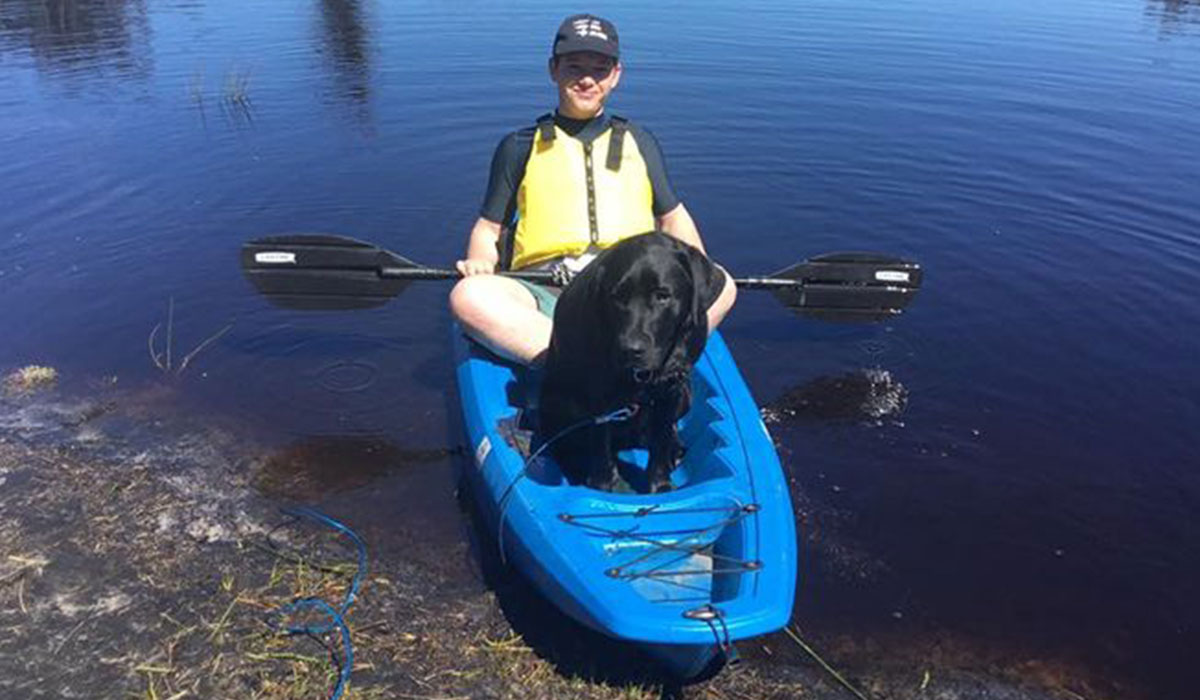 a pup and a young boy in a kayak
