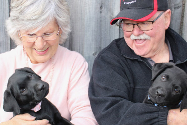 pauline and her husband holding two puppies